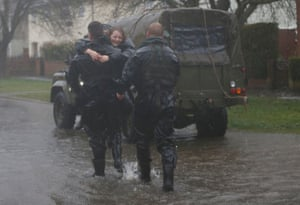 A soldier from the Royal Engineers carries a young resident onto dry land at Egham, Surrey.