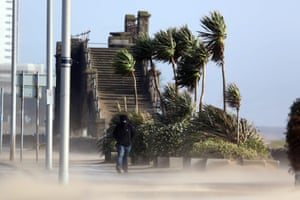 A man walks through the sand storm on Swansea seafront in south Wales.
