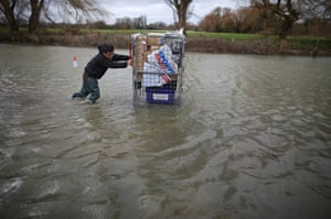 A man uses a trolley to rescue some possessions  from his flooded home in Staines, Surrey.