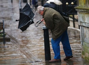 A man struggles to control his umbrella from the wind in Windsor.