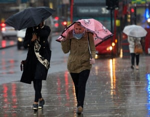 Women struggle in stormy weather in central London.