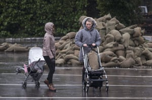 Two women use pushchairs to transport sandbags to their properties which are at risk from River Thames flood waters in Cookham, Berkshire.