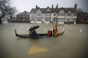 A couple promote an Italian restaurant by rowing their gondola through flood waters in Datchet.