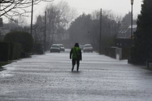 A resident walks through floodwater in  the village of Wraysbury, as rain continues to fall.