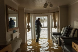 Matt Beesley looks out of the window in his flooded living room that faces onto the River Severn in Worcester.