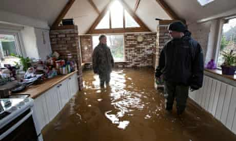 Steve Wilton and his son-in-law Ross study the damage in the kitchen of their home.