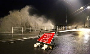 Waves break over the sea wall at Aberystwyth