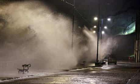 Waves break over the sea wall at high tide at Aberystwyth, west Wales