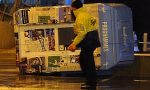 A steward walks past a fallen programme booth before the English Premier League football match between Manchester City and Sunderland was postponed due to bad weather outside the Etihad Stadium in Manchester.