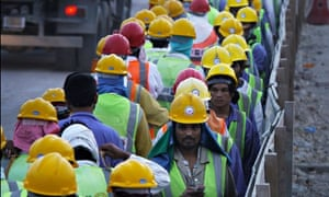 Workers at the 6am change of shift on a 2022 World Cup construction site.