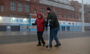 Members of the public struggle in the high winds at Blackpool promenade before the seafront was closed.