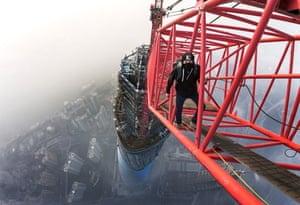 Vadim Makhorov standing on a crane on top of the the Shanghai tower