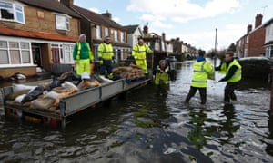 Workers deliver sandbags to a flooded street in Egham on Thursday.