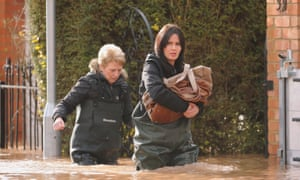 Residents of Waterworks Road in Worcester make their way through floodwater as they leave their homes.