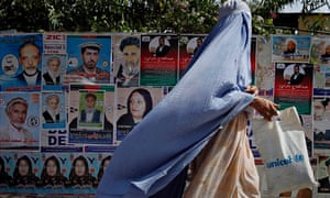 An Afghan woman walks past by election posters of parliamentary candidates in Jalalabad, Afghanistan