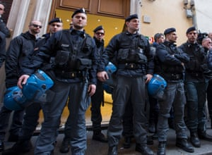 Police officers  stand in front of the entrance of the Democratic Party headquarters during leadership meeting to decide whether to yank support from Italian Premier Enrico Letta's fragile coalition government, accusing him of failing to make progress on key financial reforms, in Rome Thursday, Feb. 13, 2014.