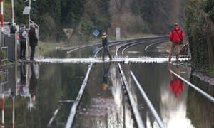 Locals cross flooded railway lines after the river Thames burst its banks in Datchet.