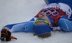 Finland's Iivo Niskanen lies on the snow at the finish line in the Men's Cross-Country Skiing 15km Classic at the 2014 Winter Olympics.