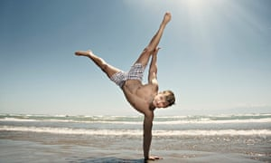A man doing a handstand on the beach.