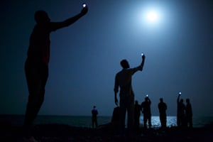 This picture released by the World Press on February 14, 2014 shows the image taken by American photographer John Stanmeyer of the VII Photo Agency and selected by the international jury of the 57th annual World Press Photo Contest as the World Press Photo of the Year 2013. The picture shows African migrants on the shore of Djibouti city at night, raising their phones in an attempt to capture an inexpensive signal from neighboring Somaliaa tenuous link to relatives abroad. The picture also won 1st Prize in the Contemporary Issues category, and was shot for National Geographic. -