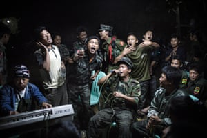 the 1st prize in the Daily Life Single category of the 2014 World Press Photo Contest by Julius Schrank, Germany, De Volkskrant, shows Kachin Independence Army fighters drinking and celebrating at a funeral of one of their commanders who died the day before, Burma,.