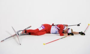 Elisa Gasparin of Switzerland collapses at the finish line in the women's 15 km individual biathlon.