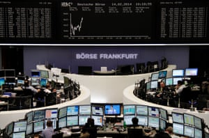 Traders are pictured at their desks in front of the DAX board at the Frankfurt stock exchange this morning.