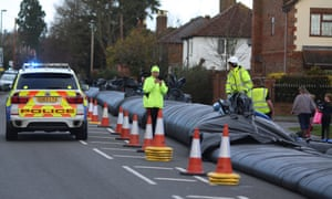 Workers install an aqua dam to protect homes from expected floodwater in Chertsey, Surrey.