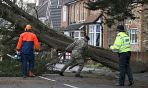 A soldier helps a tree surgeon to clear a fallen tree in Egham, Surrey