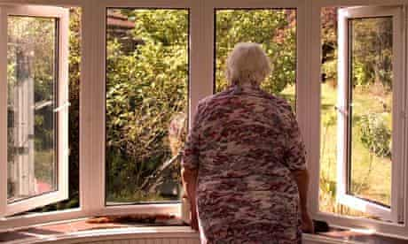An elderly woman looking out of her front room window