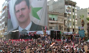 A handout picture made available by the official Syrian Arab News Agency shows Syrian citizens carrying pictures of President Bashar Assad.