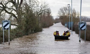 A police patrol boat floats down the flooded A361 in the Somerset Levels.