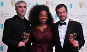 Out of this world … Mexican director Alfonso Cuarón (left) and British producer David Heyman (R) with Oprah Winfrey and their awards for an outstanding British film for Gravity.