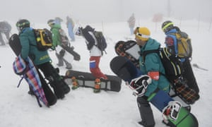 Competitors leave the course after the jury's decision to cancel the men's snowboard cross at the Sochi Winter Olympics.