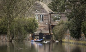 A woman pulls children in a dinghy near the Thames in Hurley.