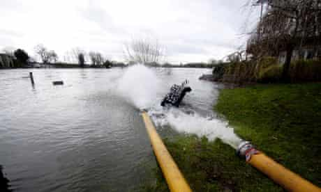 Water being pumped out of houses near the river Thames at Chertsey, Surrey