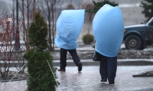 Workers protect themselves from heavy rain as they walk to the media center during the Sochi Winter Olympics.