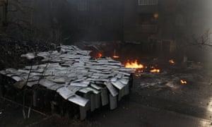 Police take cover in anti-government protests in Kiev.