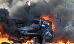 A protester throws a device at riot police.
