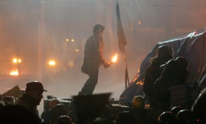 An anti-government protester prepares to throw a molotov cocktail in the centre of Kiev.