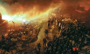 Ukrainian riot police stand in front of the fire ring around of the Independence Square.
