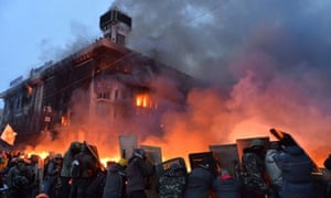 Anti-government protesters protect themselves behind shields as they clash with the police on Independence Square in Kiev early on Wednesday.
