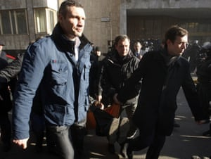 The Head of Udar or Punch party Vitali Klitschko  together with other anti-government protesters carry a wounded man during clashes with riot police in Kiev on Tuesday.