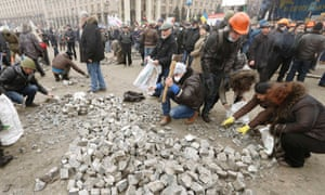 Anti-government protesters gather stones during a rally in central Kiev.