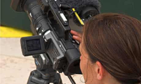 Woman videographer filming for BBC television checking LCD monitor on camera