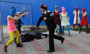 A Cossack militiaman attacks Nadezhda Tolokonnikova and a photographer as she and fellow members of Pussy Riot stage a protest performance.