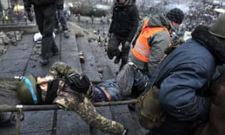 Protesters evacuate a wounded demonstrator from Kiev's Independence square after the security forces were pushed back in new clashes.
