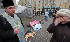 An Orthodox priest holds a cross as a woman reacts next to dead bodies following violence in Independence Square.