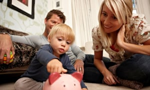 Father, mother and son putting coins in piggy bank