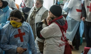 Medics embrace in the lobby of the Hotel Ukraine, which has been converted to a medical clinic and makeshift morgue.